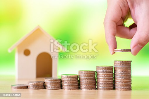 958039576istockphoto Property investment and house mortgage financial concept, Hand putting money coin stack with wooden house 1083309864