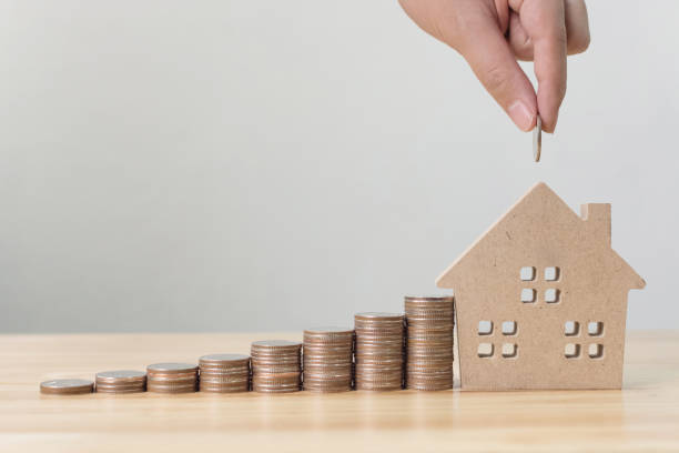 Property investment and house mortgage financial concept, Hand putting money coin stack with wooden house stock photo