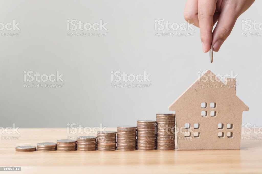 Property investment and house mortgage financial concept, Hand putting money coin stack with wooden house Property investment and house mortgage financial concept, Hand putting money coin stack with wooden house Advice Stock Photo
