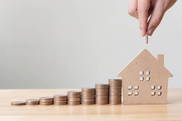 investitionen in immobilien und haus hypothek finanzkonzept, hand setzen geld münze stapel mit holzhaus - mieterhöhung stock-fotos und bilder