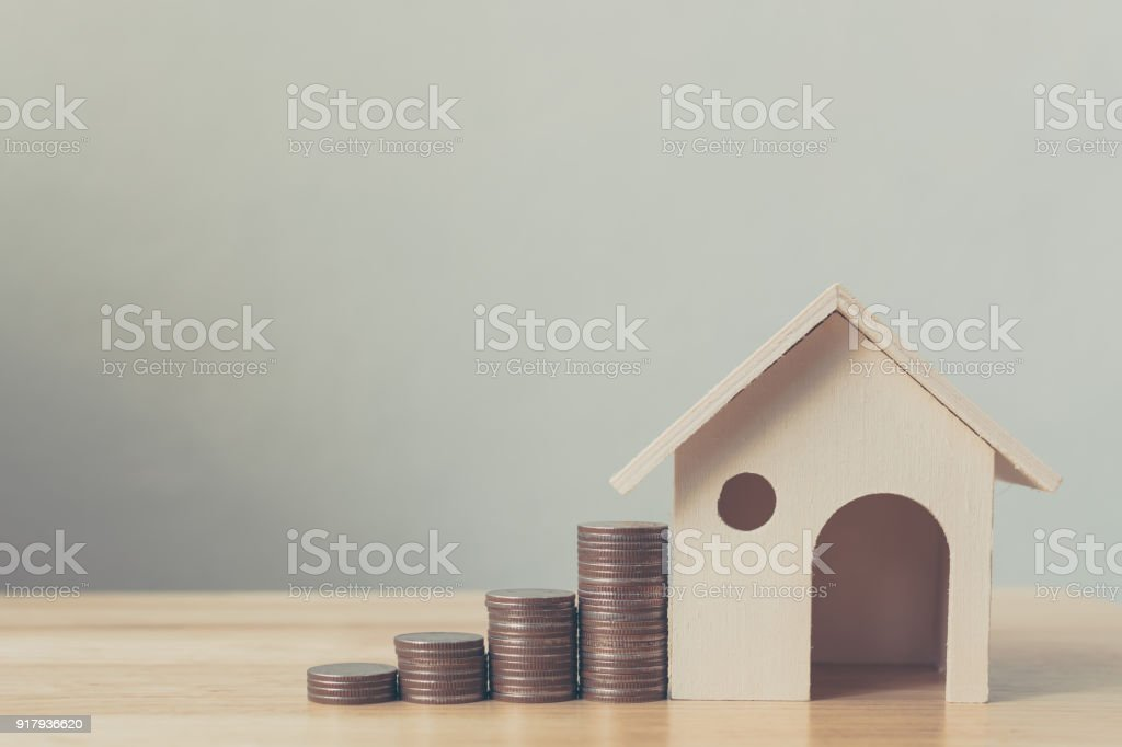 Property investment and house mortgage financial concept, House model and coin money on table for finance and banking stock photo