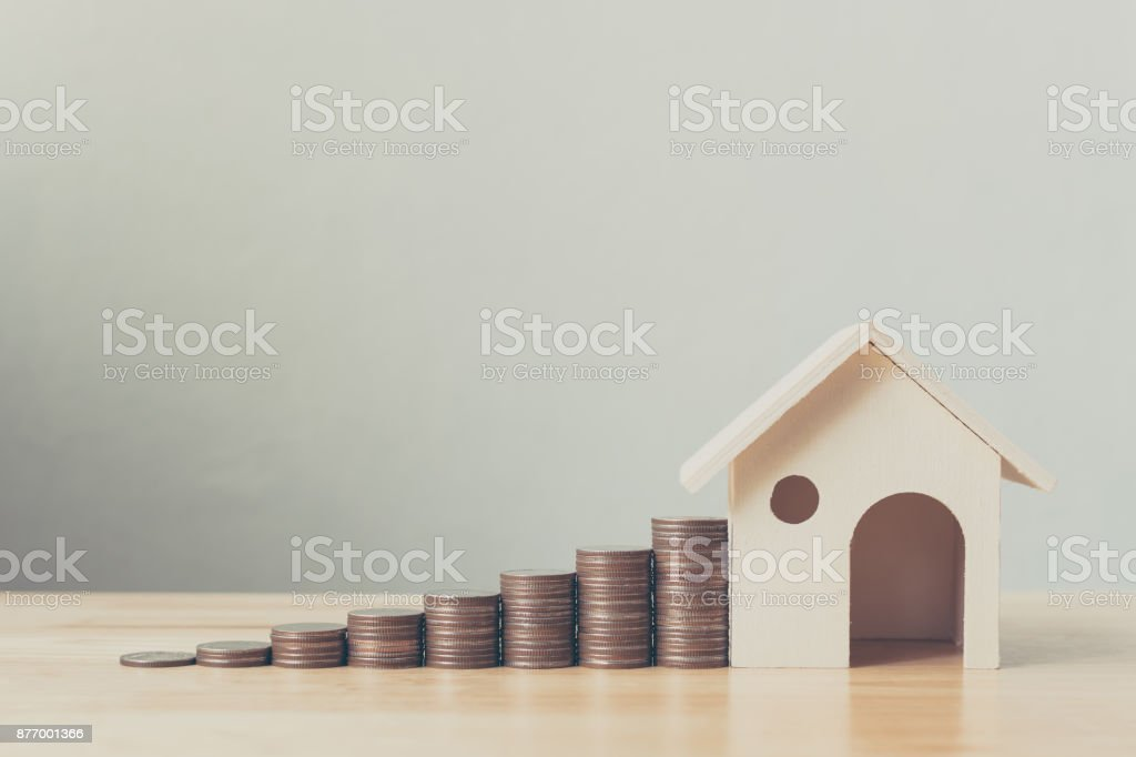 Property investment and house mortgage financial concept, Money coin stack with wooden house stock photo