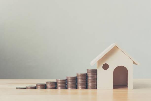 maison et immeubles de placement hypothécaire financière concept, pile de pièces d'argent avec maison en bois - prêts immobiliers et crédits photos et images de collection