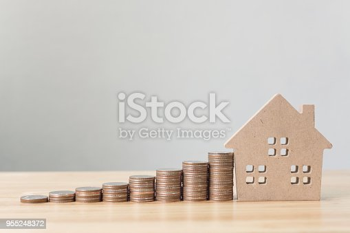 958039576 istock photo Property investment and house mortgage financial concept, Money coin stack with wooden house 955248372