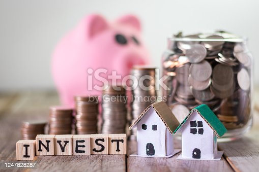 Home investment, saving money for mortgage, coins in a glass jar on wooden table background