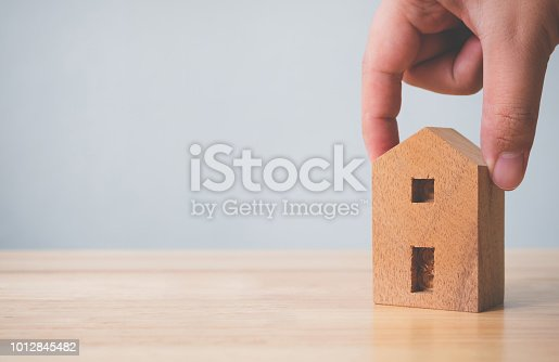 958039576istockphoto Property investment real estate and house mortgage financial concept. Hand holding wooden home on table 1012845482