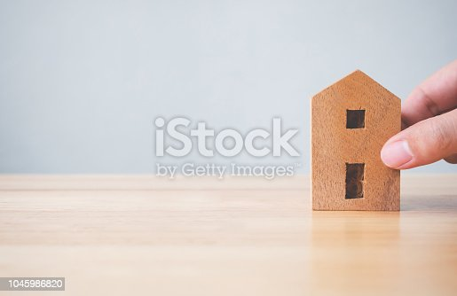958039576istockphoto Property investment real estate and house mortgage financial concept. Hand holding wooden home on table 1045986820