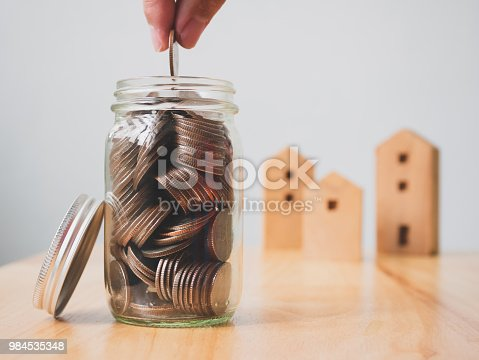 958039576istockphoto Property investment real estate and house mortgage financial concept. Hand putting money coins in jar with wooden home on table 984535348