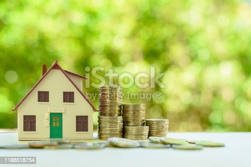 1145921132istockphoto Property investment / reverse mortgage, financial concept : Small home or house model with green door and stacks of rising coins, depicts saving money to buy a new residential asset, human basic needs 1168018754