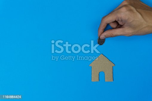 istock Property investment, savings money for buy new home concepts. A man hand holding coin over small residence house in paper on blue background and space. A sustainable investment. 1164884424