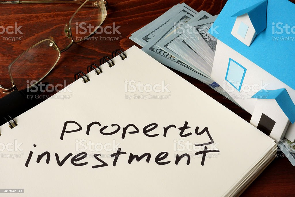 Property Investment  written on notebook with model of house. stock photo