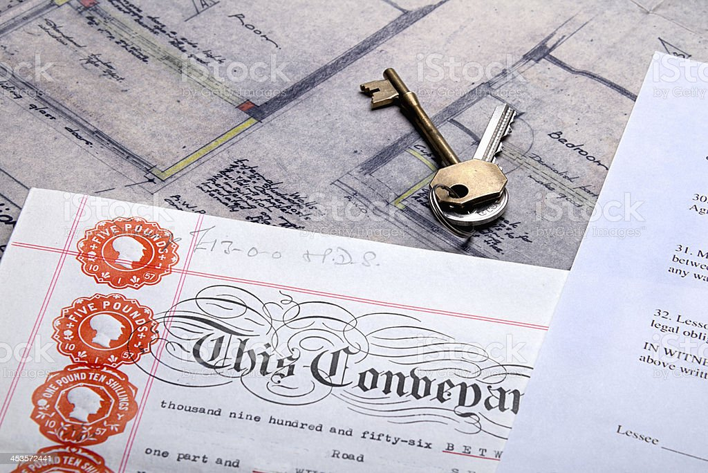 Property Mortgage deeds and house keys sit on top plans stock photo