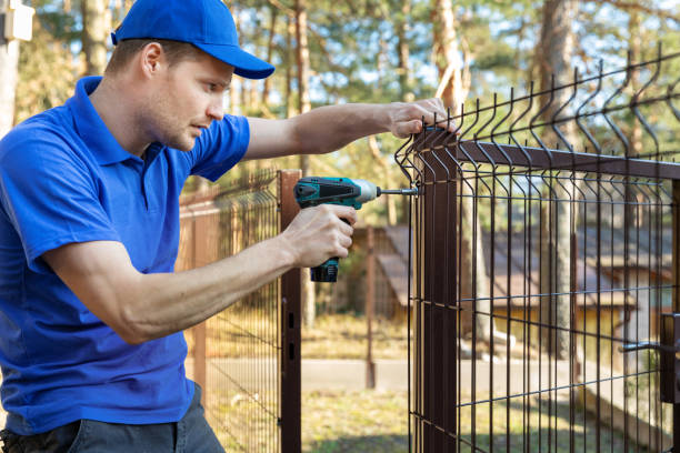 property territory fencing - man screws metal fence panel stock photo