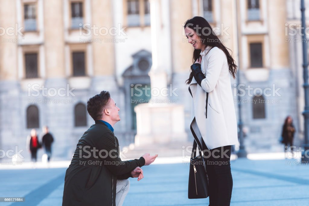Proposal in the street man asking marry to his girlfriend stock photo