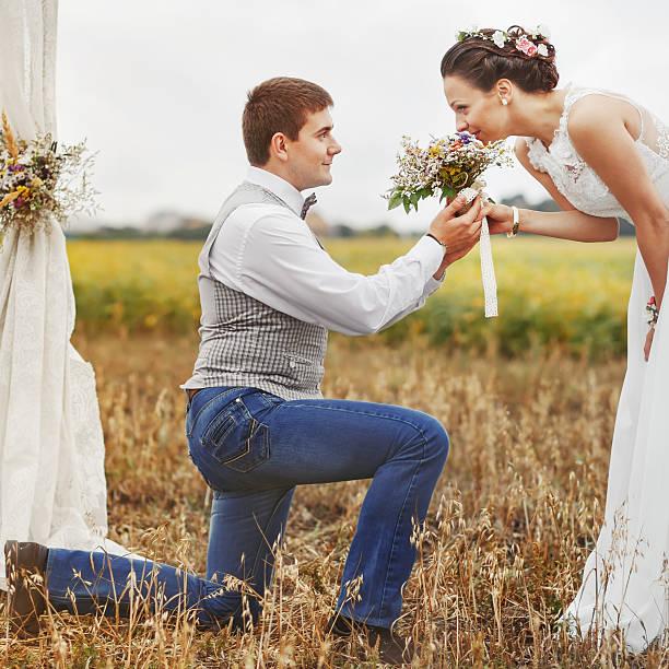 vorschlag moment happy hochzeit junge frisch verheiratet paar. - bräutigam jeans stock-fotos und bilder