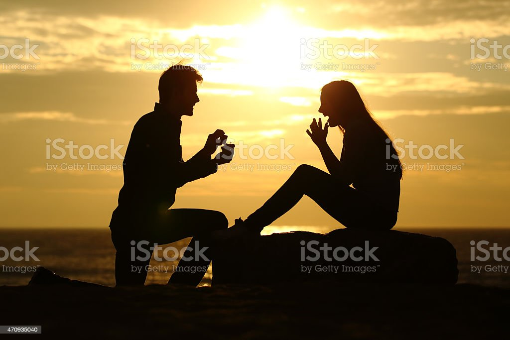 Proposal on the beach with man asking for marry stock photo