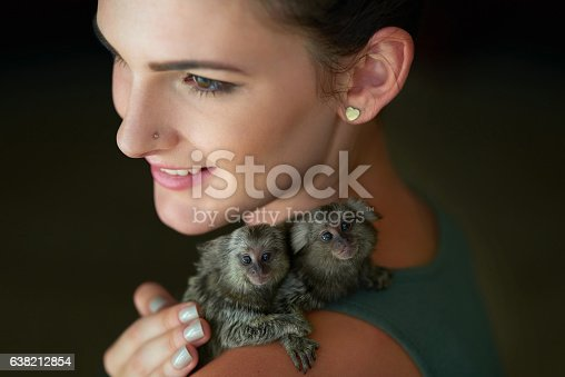 Cropped shot of an attractive young woman posing with two pigmy marmosets