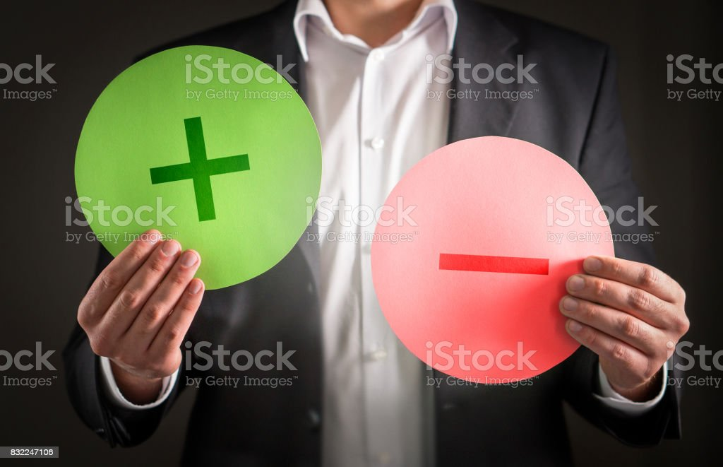 Pros and cons concept. Business man with cardboard plus and minus symbol signs. stock photo
