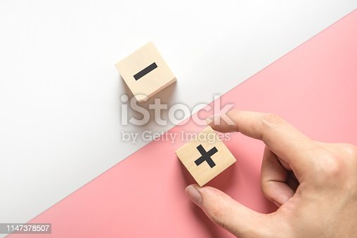 Pros and cons concept, Hand choose wood blog with plus and minus on white and pink background, flat lay, copy space, top view.