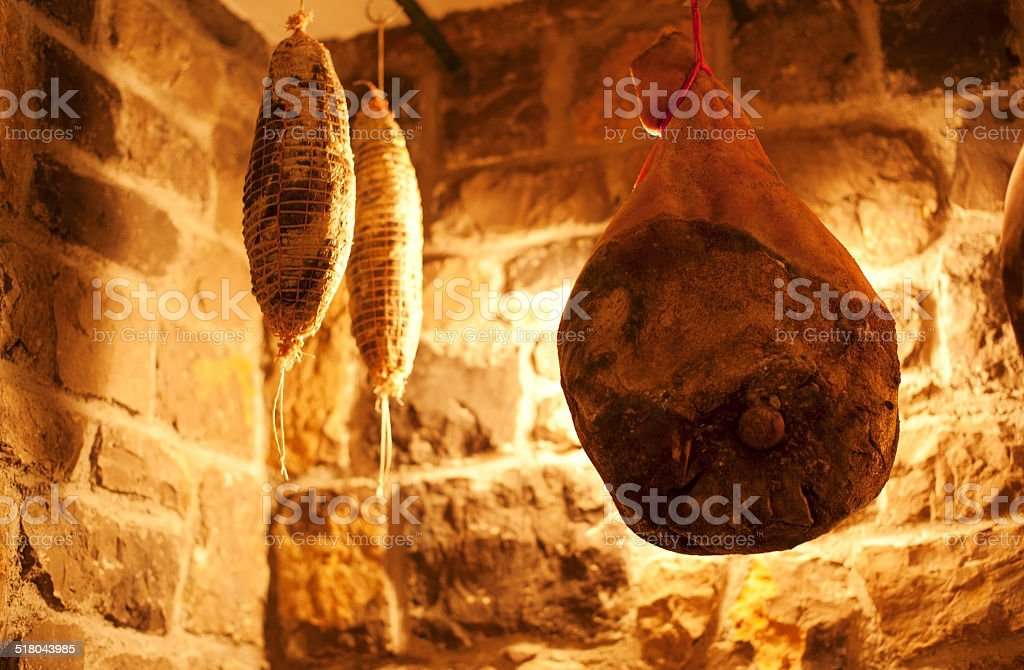 Prosciutto and Salamis Hanging in the Cellar stock photo