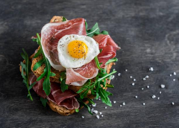 schinken, rucola und gebratenen wachteln eiern sandwich auf hölzernen hintergrund, ansicht von oben. leckeres frühstück, snack oder vorspeise - ei sandwiches stock-fotos und bilder