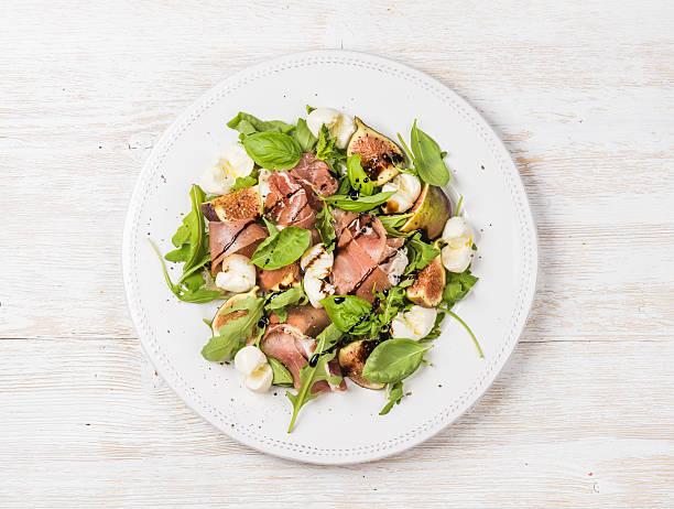 Prosciutto, arugula, basil, figs salad and glass of red wine stock photo