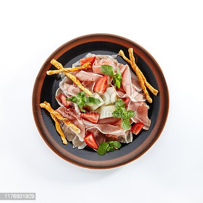 Thinly sliced Italian prosciutto, prosciutto crudo or crudo with melon, strawberry and crostini close up isolated on white background. Top View of dry-cured uncooked ham with green mint leaves