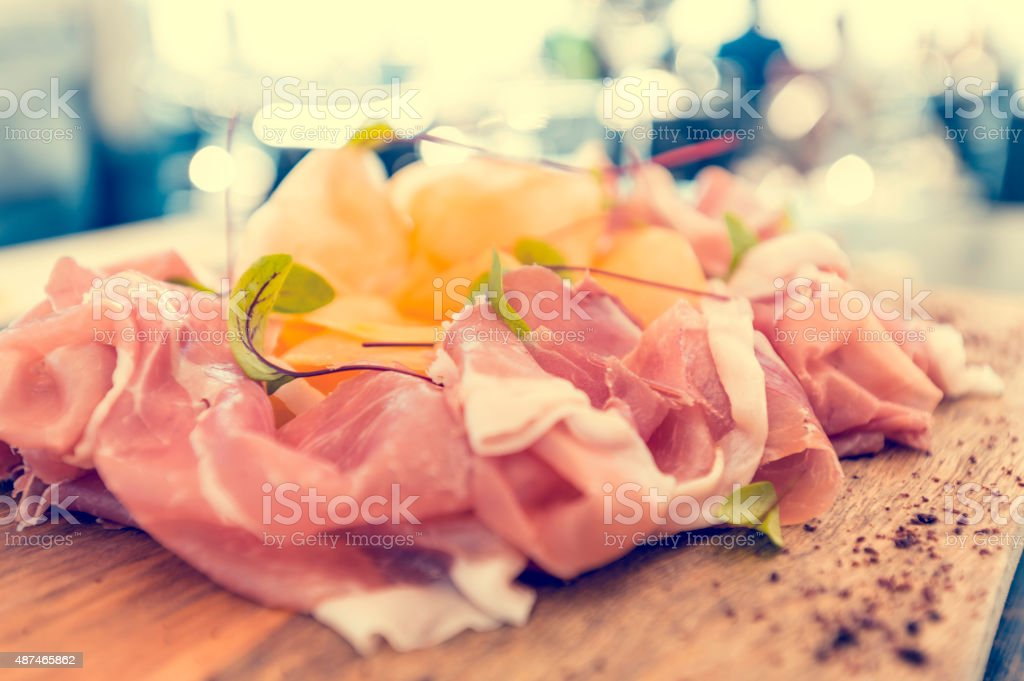Prosciutto garnished with rockmelon in a restaurant. stock photo