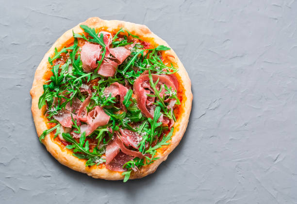 Prosciutto homemade pizza on grey background, top view. Delicious appetizers, snack, tapas in mediterranean style. Free space stock photo