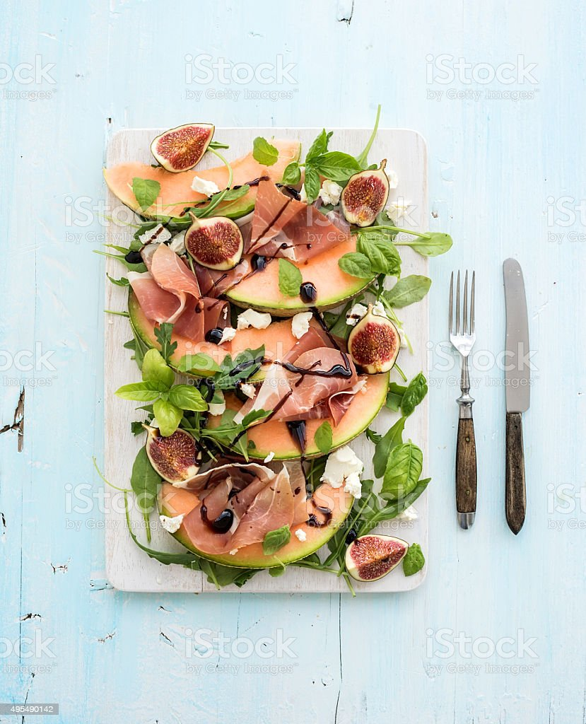 Prosciutto, melon, fig and soft cheese salad on a white stock photo