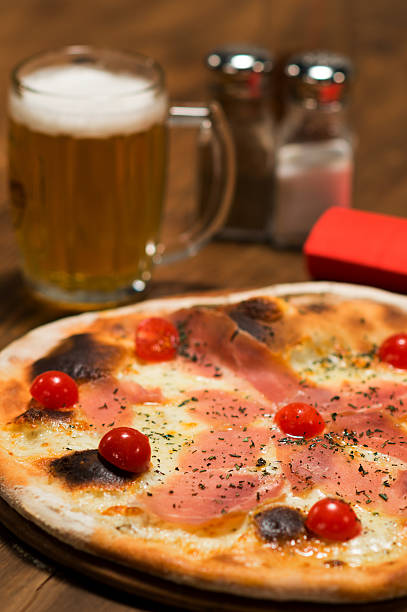 Prosciutto Pizza with a glass of beer stock photo