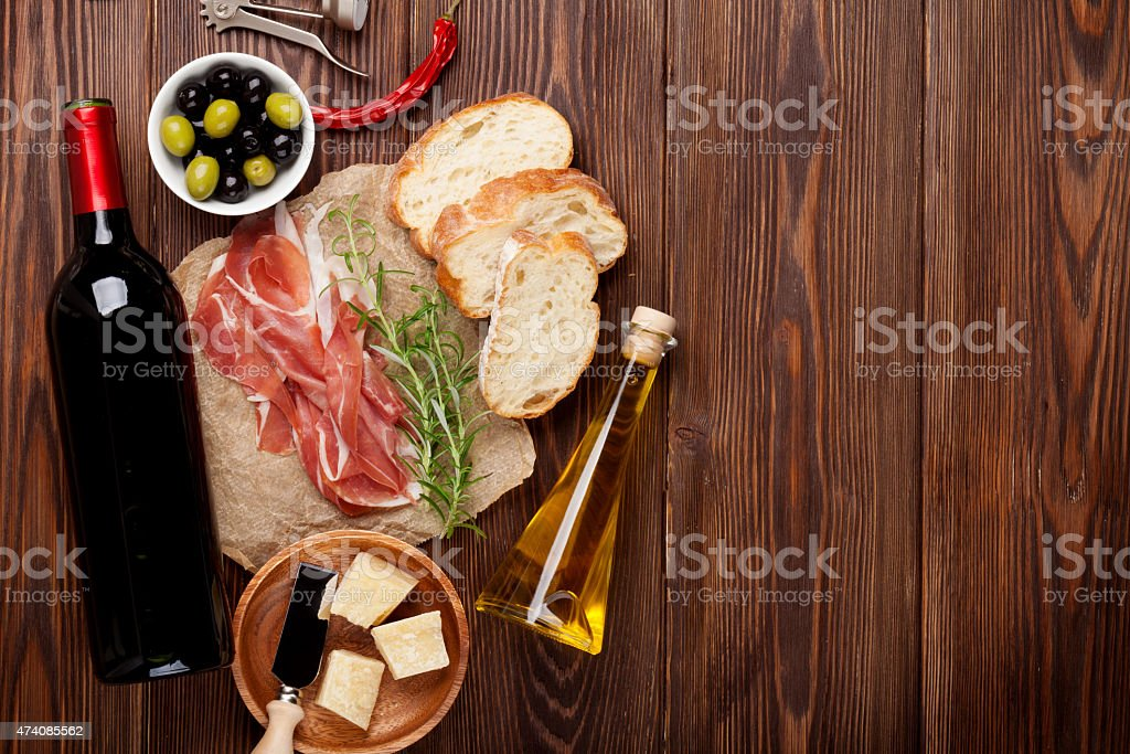 Prosciutto, wine, oils, parmesan, and olive oil against wood stock photo