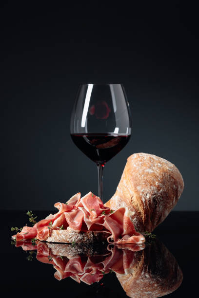 Prosciutto with ciabatta, red wine and thyme on a black background. stock photo