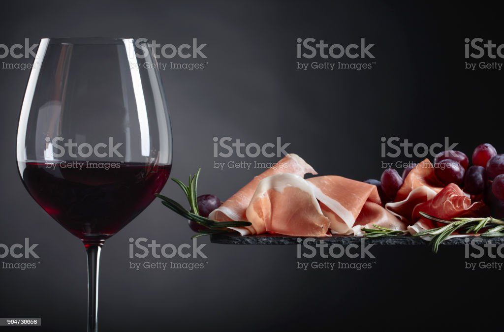 Prosciutto with rosemary and glass of red wine. royalty-free stock photo