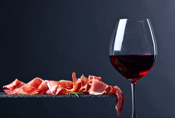 prosciutto with rosemary and red wine on a black  background - pökeln stock-fotos und bilder