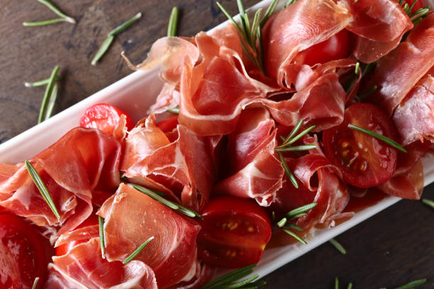 Prosciutto with  rosemary and tomatoes on a old wooden table in white dish. stock photo
