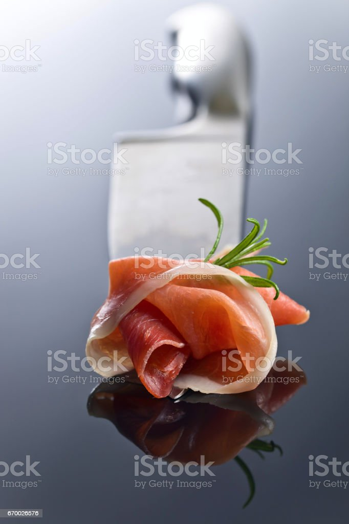 Prosciutto with  rosemary  on a big meat knife stock photo