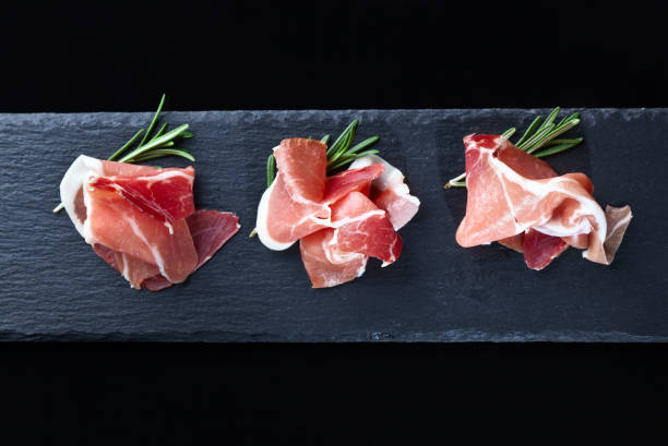 prosciutto with rosemary on a black background stock photo
