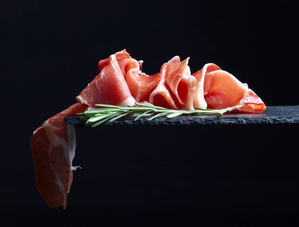 prosciutto with rosemary on a black  background - 이베리아 반도 뉴스 사진 이미지