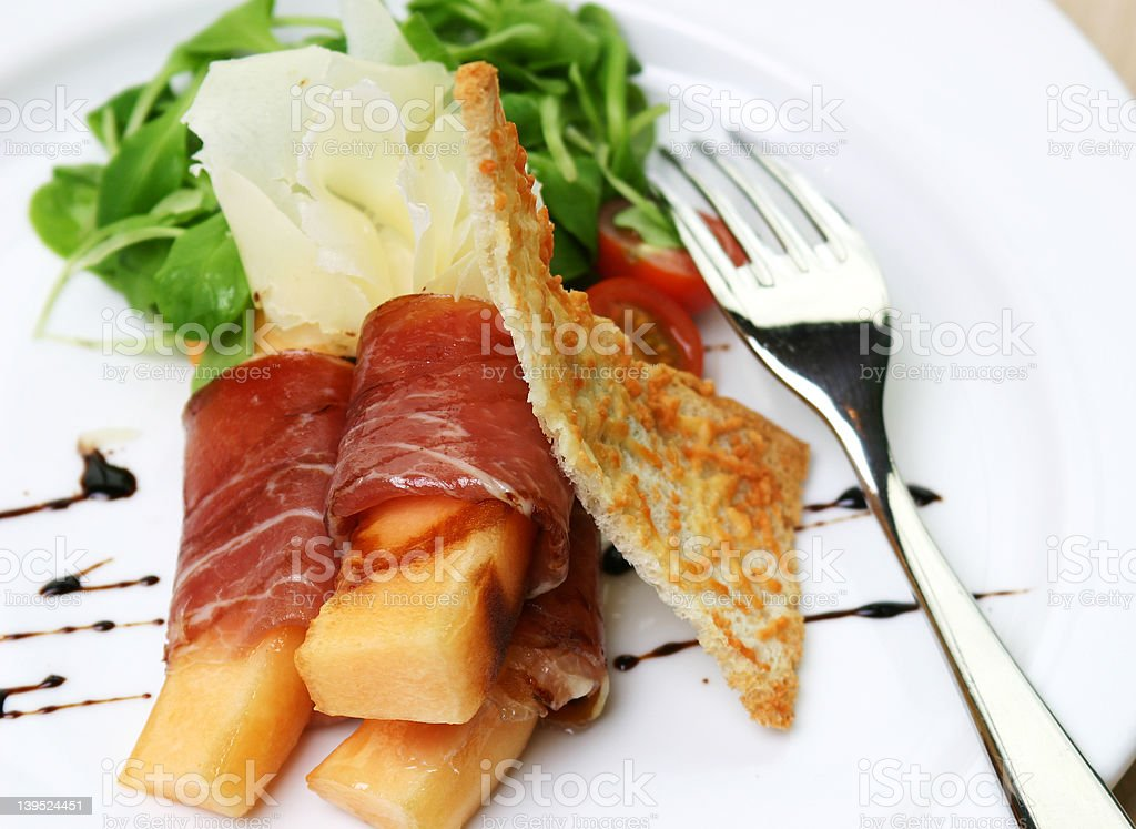 Proscuitto ham rolled around fresh melon stock photo