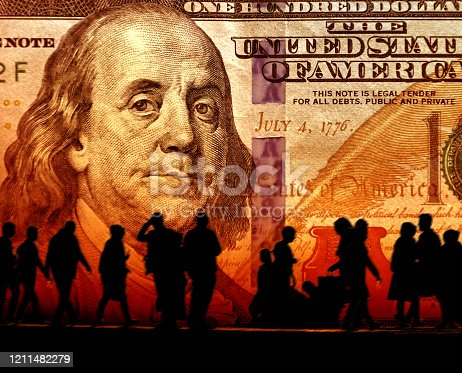 Conceptual image of silhouetted crowd of people and American One Hundred Dollar Bill