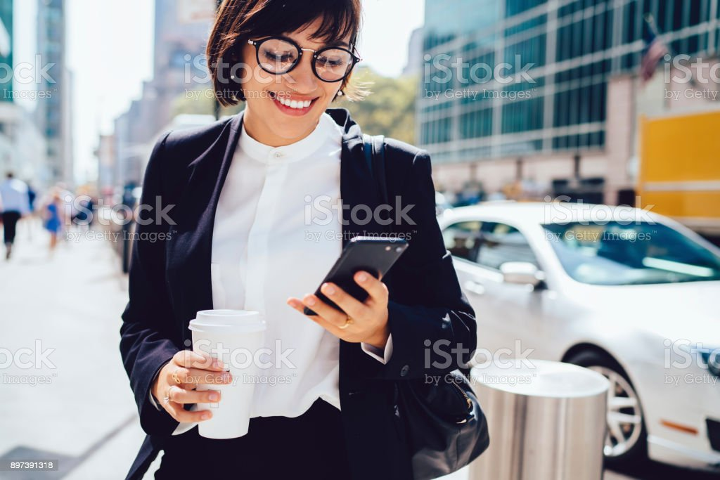 Prosperous Female entrepreneur in formal wear smiling while reading message on cellular walking on street, cheerful businesswoman satisfied with successful news sending feedback on phone strolling - foto stock