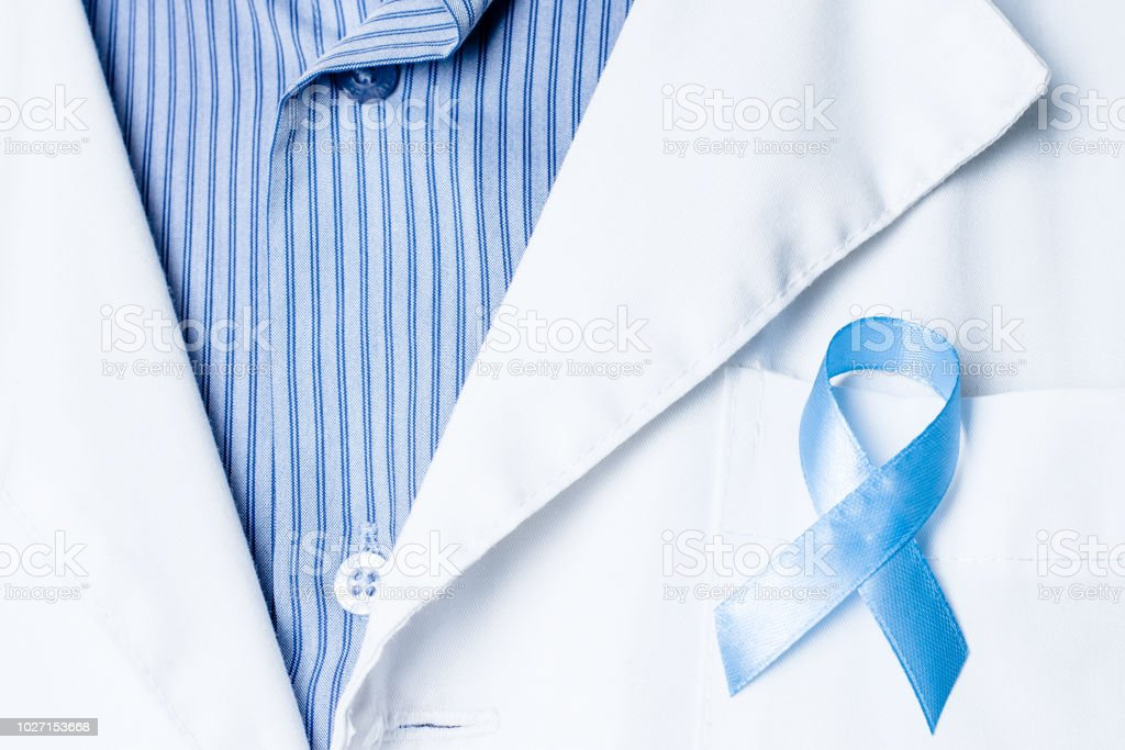 Prostate cancer awareness. Blue ribbon in doctor hand. Man, male...