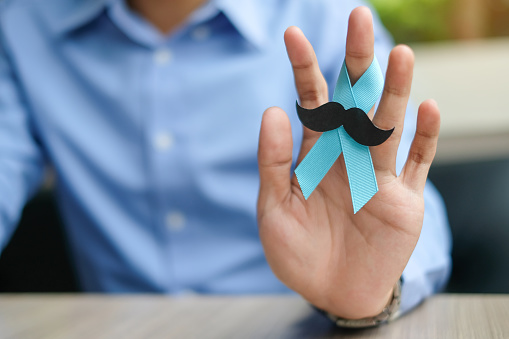 1168142443 istock photo Prostate Cancer Awareness, Man hand holding light Blue Ribbon with mustache for supporting people living and illness. Men Healthcare and World cancer day concept 1168524051