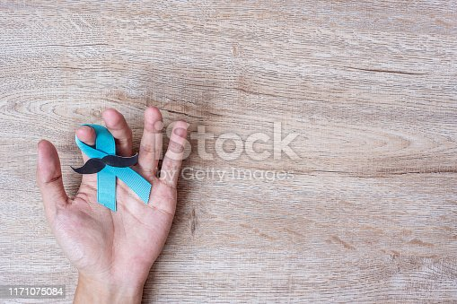 868356038istockphoto Prostate Cancer Awareness, Man holding light Blue Ribbon with mustache on wooden background for supporting people living and illness. Men Healthcare and World cancer day concept 1171075084