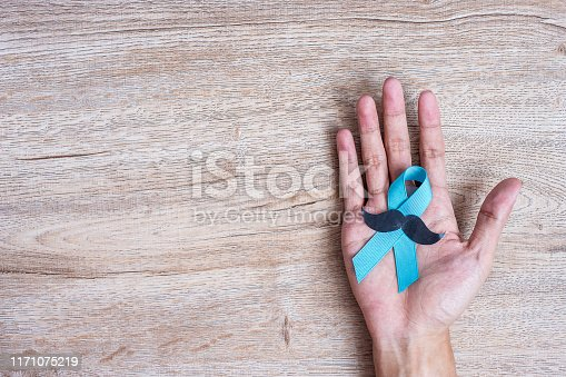 868356038istockphoto Prostate Cancer Awareness, Man holding light Blue Ribbon with mustache on wooden background for supporting people living and illness. Men Healthcare and World cancer day concept 1171075219