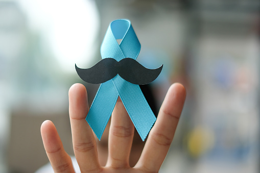1168142443 istock photo Prostate Cancer Awareness, wonan hand holding light Blue Ribbon with mustache for supporting people living and illness. Men Healthcare and World cancer day concept 1168524057