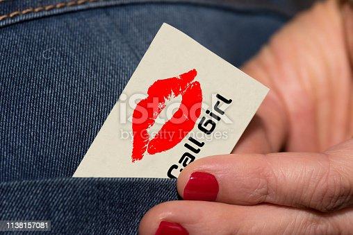 Eine Prostituierte holt eine Visitenkarte aus der Hosentasche ihrer Jeans heraus