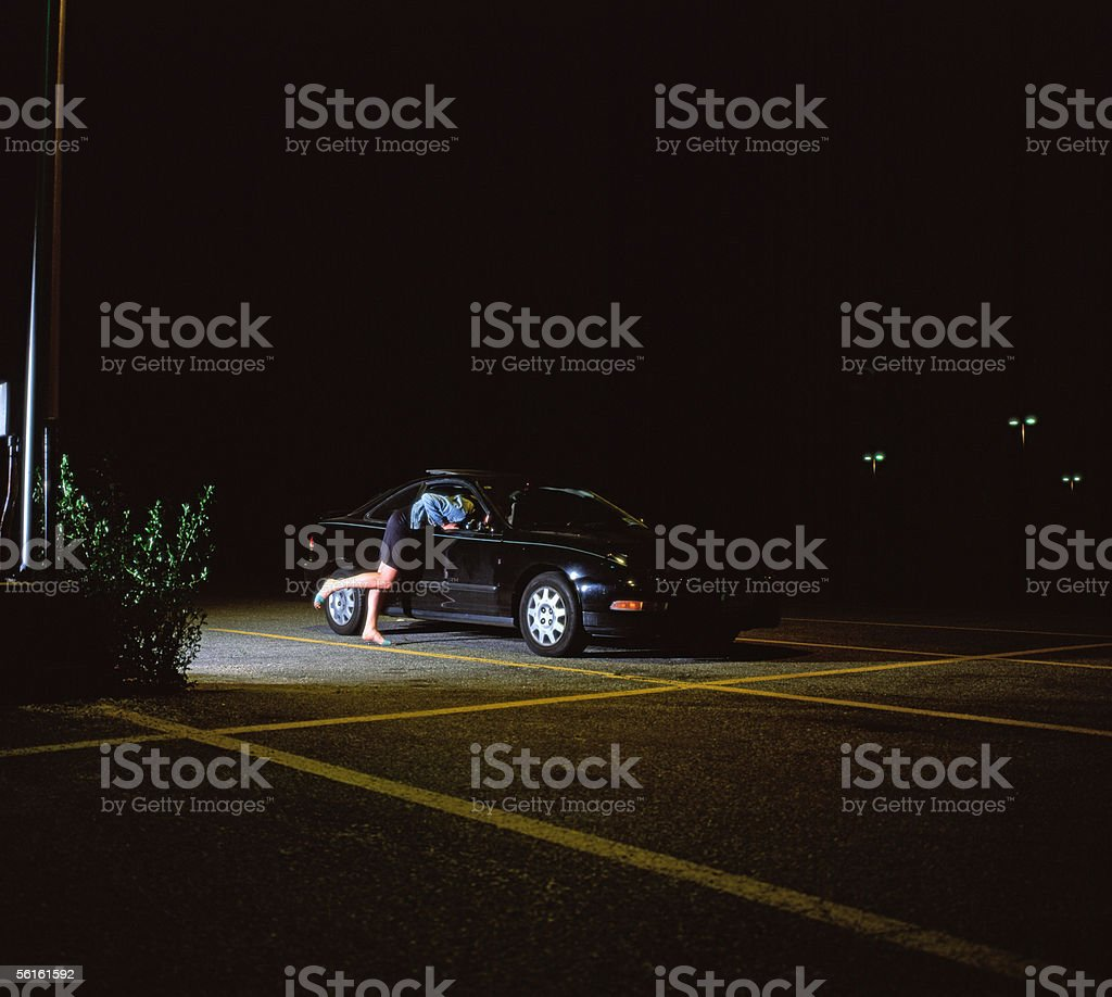 A prostitute leaning into a car stock photo