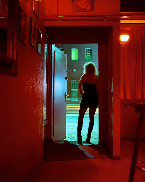Prostitute Standing in Nightclub Doorway Looking Out stock photo